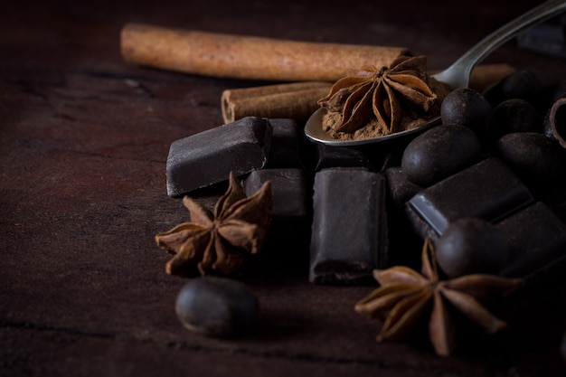 木製の表面にブラックチョコレート、スパイス、ティースプーン