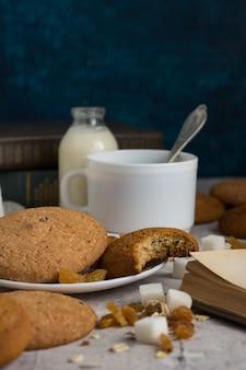 Овсяное печенье ручной работы, книги, хлопья овсяные, чашка кофе с молоком, изюм на светлой поверхности. концепция завтрака