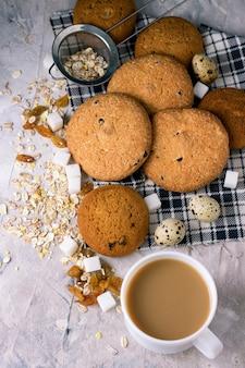 石の表面にミルクとオートミールクッキーとコーヒーのカップ。白いセラミックカップ、オートミール、レーズン、角砂糖。朝食シーン