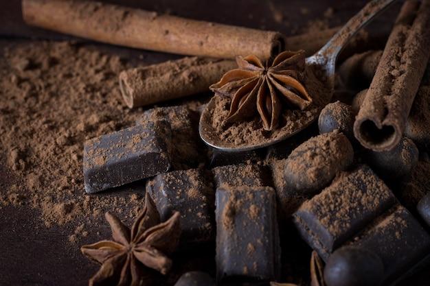 Черный шоколад, специи, чайная ложка, какао, корица на деревянной поверхности