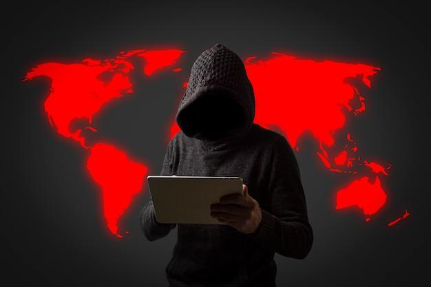フード付きのパーカーを着た顔の見えない男が暗い壁に手でタブレットを持っています。ユーザーデータのハッキングの概念。ハッキングされたロック、クレジットカード、クラウド、メール、パスワード、個人ファイル