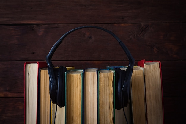 ダークウッドの壁に折りたたまれた本を置くヘッドフォン