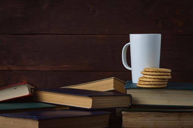 ホットコーヒーと白いカップ、暗い背景の木に展開された本のクッキー