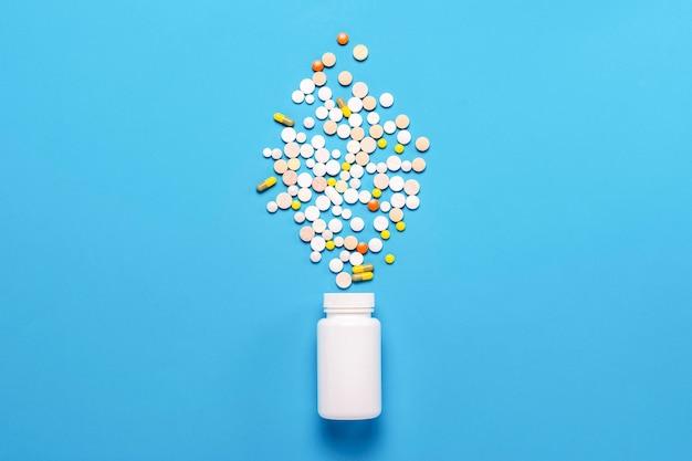 白いボトルと青色の背景にマルチカラーの錠剤。医薬品、医学、薬物および疾患の治療の概念。フラット横たわっていた、トップビュー