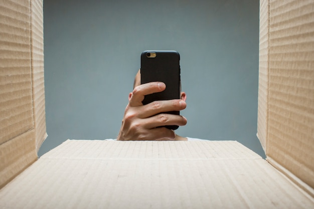 男が電話で箱の中身の写真を撮ります。注文、貨物、商品を受け取るという概念。破損した注文。