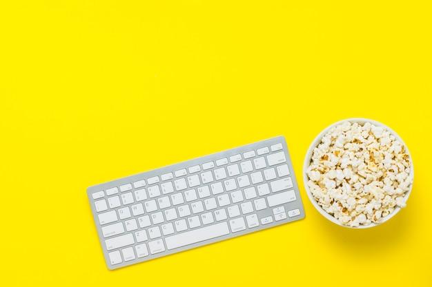 Клавиатура и чаша с попкорном на желтом фоне. концепция просмотра фильмов, сериалов, шоу, спортивных онлайн. плоская планировка, вид сверху.