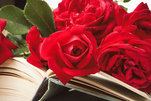 Красные розы на открытой книге на светлой каменной поверхности. понятие романтической литературы. плоская планировка, вид сверху
