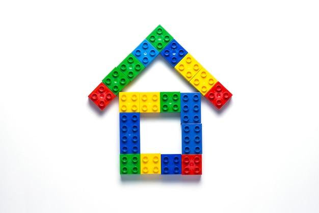 白い背景の上の子供のデザイナーからの家。家を建てる、建てるのコンセプト。フラット横たわっていた、トップビュー。