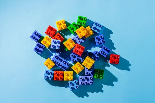 青色の背景に子供のデザイナーからの多色の詳細。フラット横たわっていた、トップビュー。