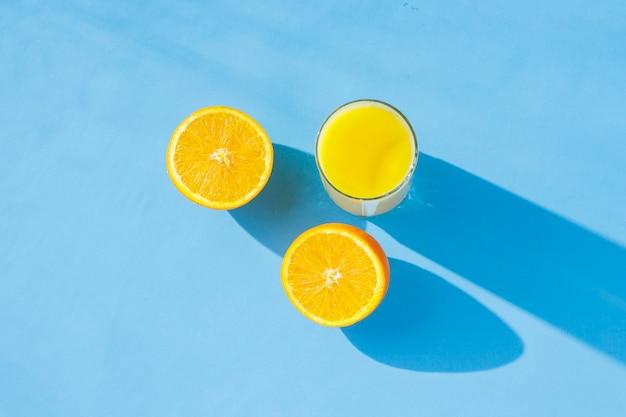 オレンジジュースと青色の背景にオレンジのガラス。ビタミン、熱帯、夏の概念。自然光。フラット横たわっていた、トップビュー。