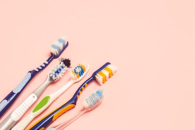 ピンクの背景にいくつかの異なる使用された歯ブラシ。歯ブラシの変更コンセプト、口腔衛生、大規模でフレンドリーな家族、歯ブラシの選択。フラット横たわっていた、トップビュー。