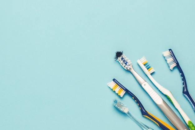 青色の背景にいくつかの異なる使用された歯ブラシ。歯ブラシは、コンセプト、口腔衛生、大規模でフレンドリーな家族を変えます。フラット横たわっていた、トップビュー。