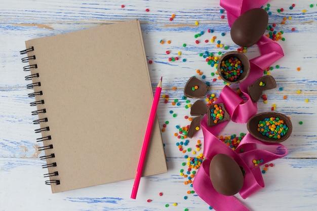 Пасхальные шоколадные яйца, розовая лента, блокнот и цветные карандаши, пасхальные разноцветные конфеты на старой белой деревянной поверхности