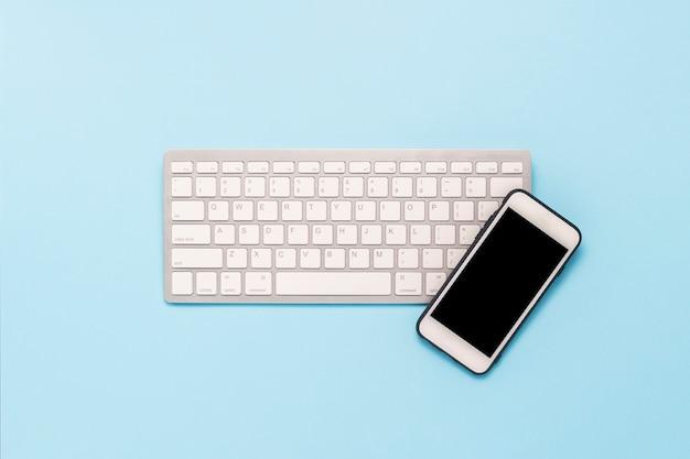 青色の背景にキーボードと白の携帯電話。ビジネスコンセプト、事務、モバイルアプリ、ウェブサイト。フラット横たわっていた、トップビュー。