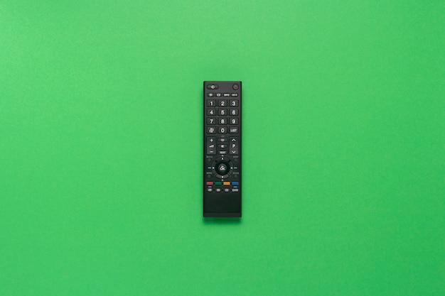 緑の背景に黒のリモコン。テレビ、映画、テレビ番組、スポーツのコンセプト。フラット横たわっていた、トップビュー。