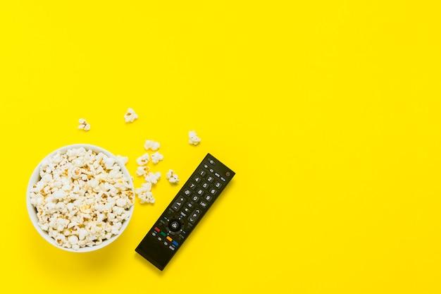 黄色の背景にポップコーンとテレビのリモコンのボウル。テレビ、映画、テレビシリーズ、スポーツ、ショーを観るコンセプト。フラット横たわっていた、トップビュー。