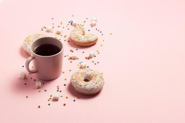 一杯のコーヒー、ピンクの背景に新鮮なおいしい甘いドーナツ。ファーストフード、ベーカリー、朝食、お菓子のコンセプトです。ミニマリズム。フラット横たわっていた、トップビュー、コピースペース。