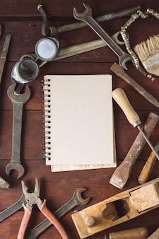 Винтажный рабочий инструмент, тетрадь на темной деревянной поверхности. концепция день отца. плоская планировка, вид сверху