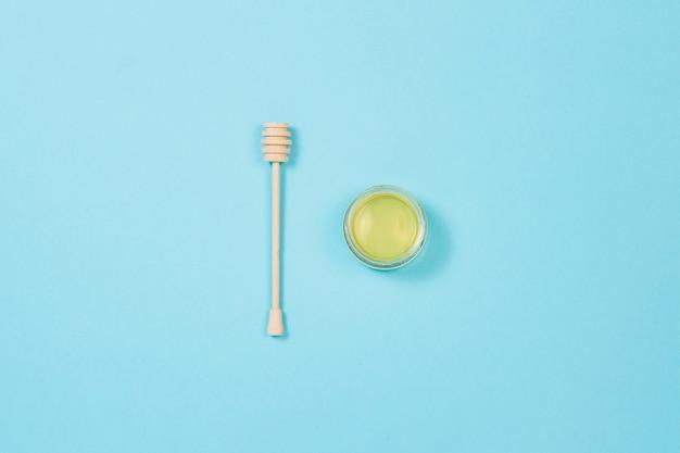 新鮮な蜂蜜の瓶と青色の背景に木製ひしゃく。フラット横たわっていた、トップビュー