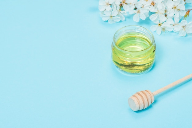 新鮮な蜂蜜と木製のひしゃくの瓶と青の背景に白い花を持つリンゴの木の枝。フラット横たわっていた、トップビュー