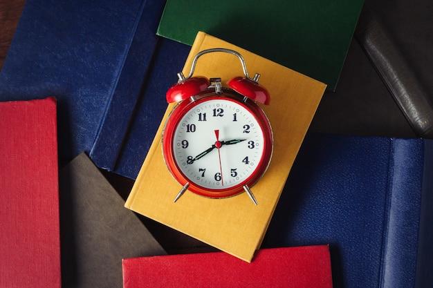 暗い木製の表面に赤い目覚まし時計と展開された本。上面図