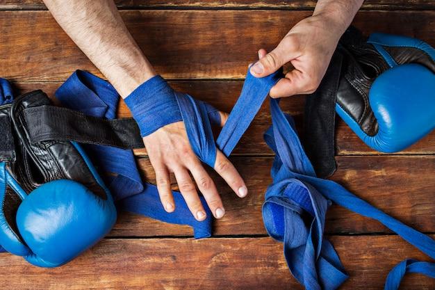 木製の表面でボクシングの試合の前に彼の手で男の包帯ボクシングテープ。ボクシングのトレーニングや戦闘のためのトレーニングの概念。フラット横たわっていた、トップビュー