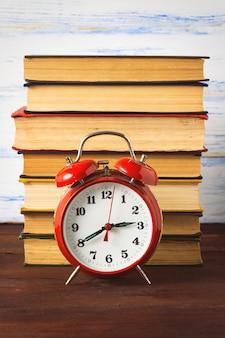 赤い目覚まし時計と木製の表面の本の山