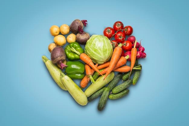 青色の背景に新鮮な有機野菜。農場野菜の購入、健康管理、収穫の概念。ハート形。カントリースタイル、ファームフェア。フラット横たわっていた、トップビュー