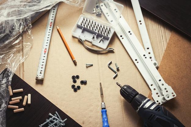 Инструменты, мебельные детали, упаковочная пленка, шурупы на листе картона. сборка мебели вручную. концептуальная мастерская. плоская планировка, вид сверху