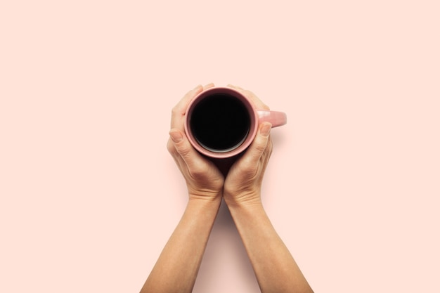 Две руки, держа чашку с горячим кофе на розовом фоне. концепция завтрак с кофе или чаем. доброе утро, ночь, бессонница. плоская планировка, вид сверху
