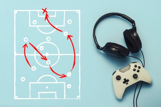 Наушники и геймпад на синем фоне. добавлена отрисовка с тактикой игры. футбол. концепция компьютерных игр, развлечений, игр, отдыха. плоская планировка, вид сверху.