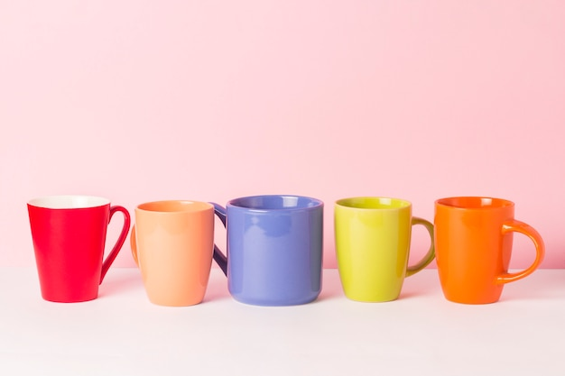 Много разноцветных чашек кофе или чая на розовом фоне. концепция дружной компании, большой семьи, встречи с друзьями за чашкой чая или кофе.
