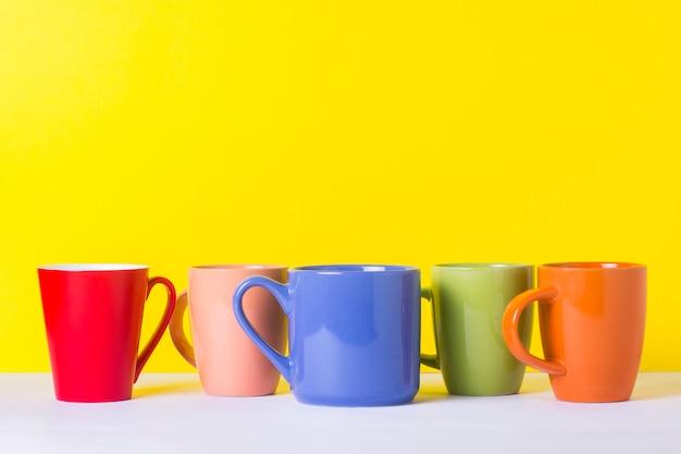 Много разноцветных чашек кофе или чая на желтом фоне. концепция дружной компании, большой семьи, встречи с друзьями за чашкой чая или кофе.