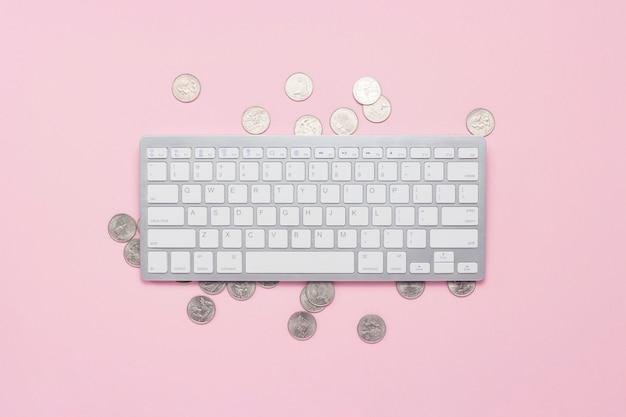 キーボードとピンクの背景のコイン。ドル記号インターネット、遠隔作業での収入の概念。フラット横たわっていた、トップビュー。