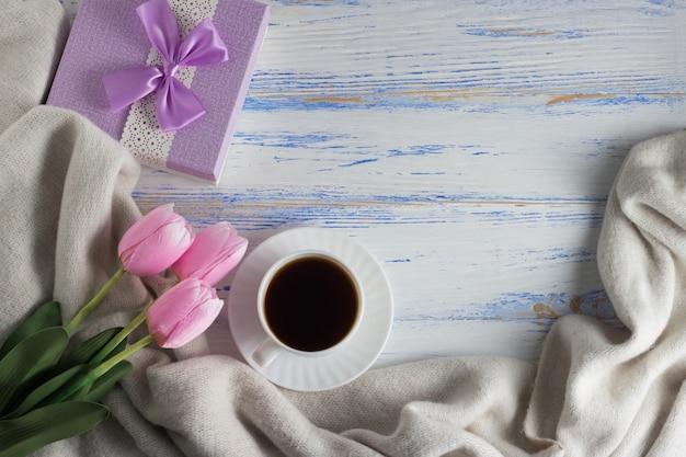 白い木製の表面にピンクのチューリップ、スカーフ、コーヒーカップ、ギフトボックス。コピースペース。フラット横たわっていた、トップビュー