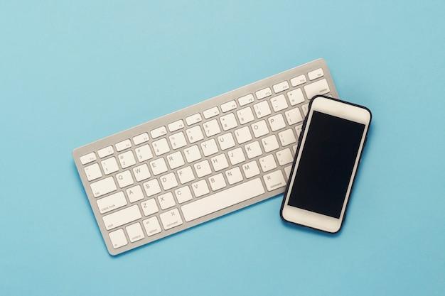 Клавиатура и белый мобильный телефон на синем фоне. бизнес-концепция, офисная работа, мобильное приложение и веб-сайт. плоская планировка, вид сверху