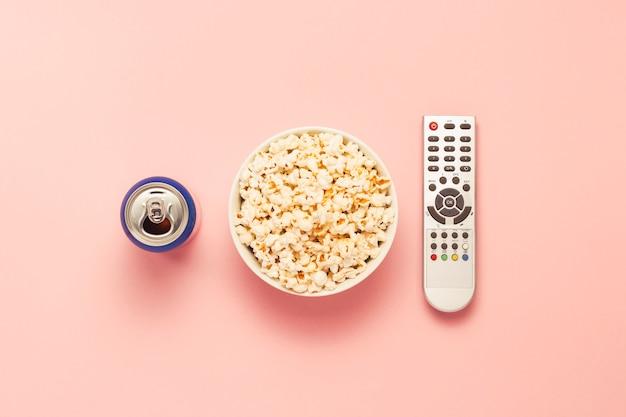ポップコーンのボウル、テレビのリモコン、ピンクの背景に飲み物の瓶。テレビ、映画、テレビシリーズ、スポーツ、番組を観るコンセプト。フラット横たわっていた、トップビュー。