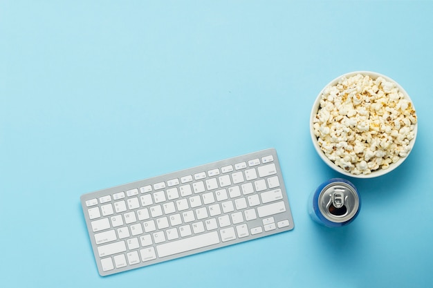 キーボードとブリキ缶、ドリンク、栄養ドリンク、青色の背景にポップコーンのボウル。映画、テレビ番組、スポーツイベントをオンラインで見るというコンセプト。フラット横たわっていた、トップビュー