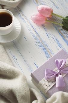 Чашка с кофе, шарф, подарок, тюльпаны на белом деревянном столе. концепция весны