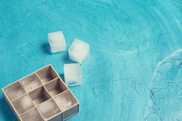 Кубики льда и силиконовые формы на фоне голубого камня. концепция производства льда. плоская планировка, вид сверху