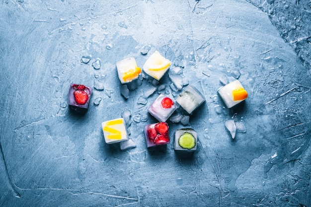 フルーツと石の青い背景に壊れた氷のアイスキューブ。ミント、ストロベリー、チェリー、レモン、オレンジ。フラットレイ、トップビュー