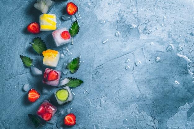 Кубики льда с фруктами и сломанный лед на камне синий фон с листьями мяты и свежих фруктов. мята, клубника, вишня, лимон, апельсин. плоская планировка, вид сверху