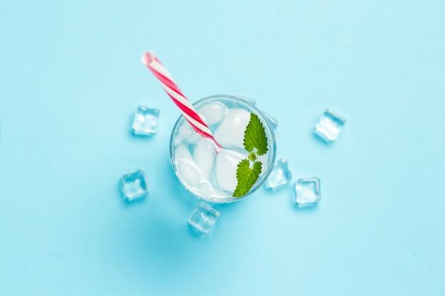 氷と青色の背景にミントの冷たいさわやかな水のガラス。アイスキューブ。暑い夏、アルコール、冷たい飲み物、喉の渇き、バーの概念。フラット横たわっていた、トップビュー