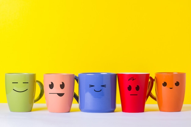 Много разноцветных чашек с забавными лицами на желтом фоне. концепция дружной компании, большой семьи, встречи с друзьями за чашкой чая или кофе, день отца, офис, день босса.
