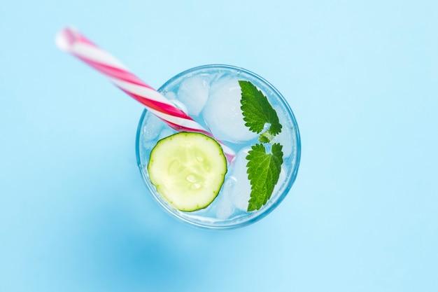 Стакан холодной и освежающей воды со льдом, мята и огурец на синем фоне. кубик льда. понятие жаркого лета, алкоголь, прохладительные напитки, утоление жажды, бар. плоская планировка, вид сверху