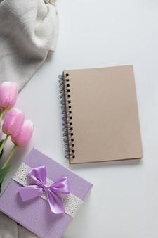 Блокнот, шарф, тюльпаны, подарочные коробки на белой поверхности. концепция весны. плоская планировка, вид сверху