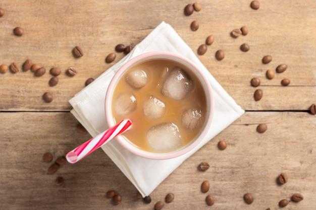 さわやかで爽やかなアイスコーヒーをグラスに注ぎ、コーヒーの粒を木製のテーブルに。コンセプトのコーヒーショップ、喉の渇きを癒す、夏。フラット横たわっていた、トップビュー