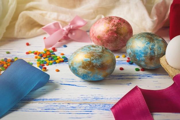 Пасхальные яйца, сладости, ленты на белом деревянном столе