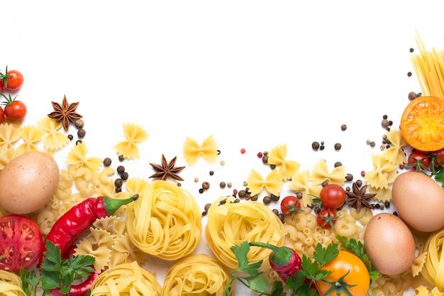さまざまな種類のイタリアンパスタ、巣、スパゲッティ、スパイス、赤唐辛子、鶏の卵、トマト、チェリー、ライトホワイトストーンサーフェス。フラット横たわっていた、トップビュー