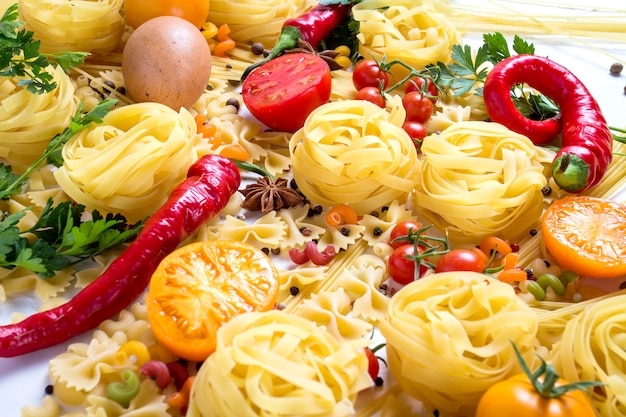 Итальянская паста разных видов со специями, красным острым перцем, куриными яйцами, желтыми и красными помидорами на белой поверхности